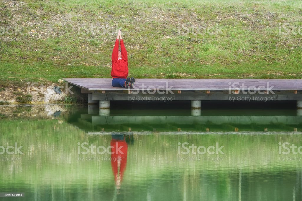 Mature woman doing yoga outdoors by lake stock photo