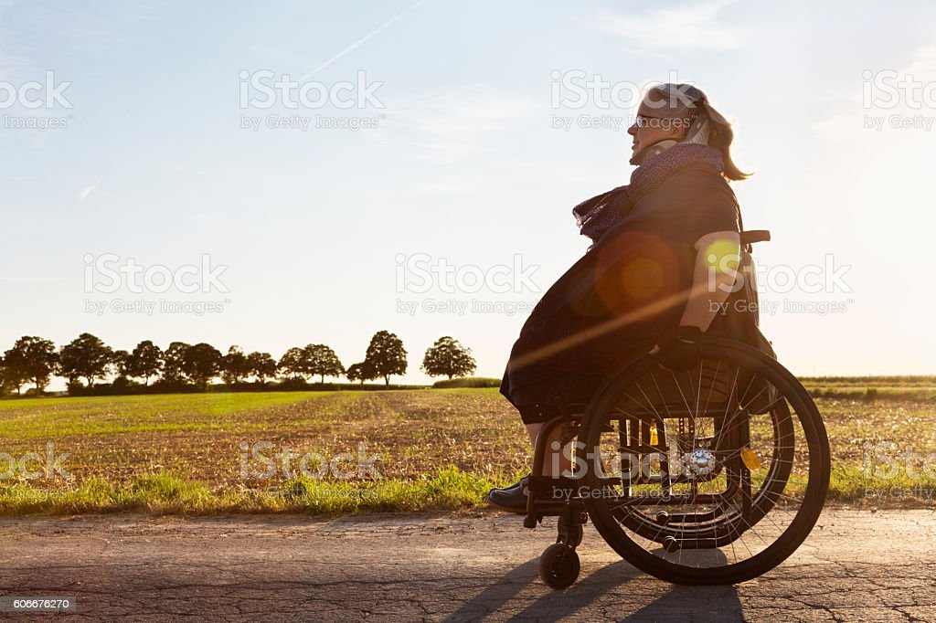 mature woman driving in wheelchair outdoors summer evening stock photo