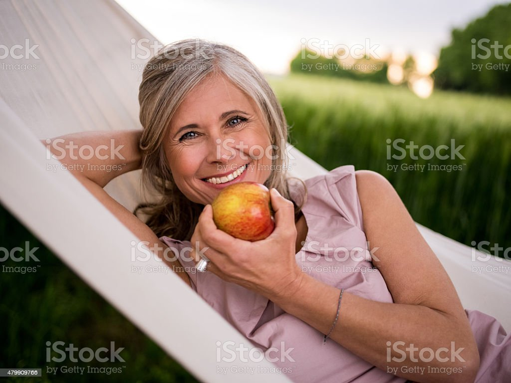Mature woman eating a fresh apple while relaxing outdoors stock photo