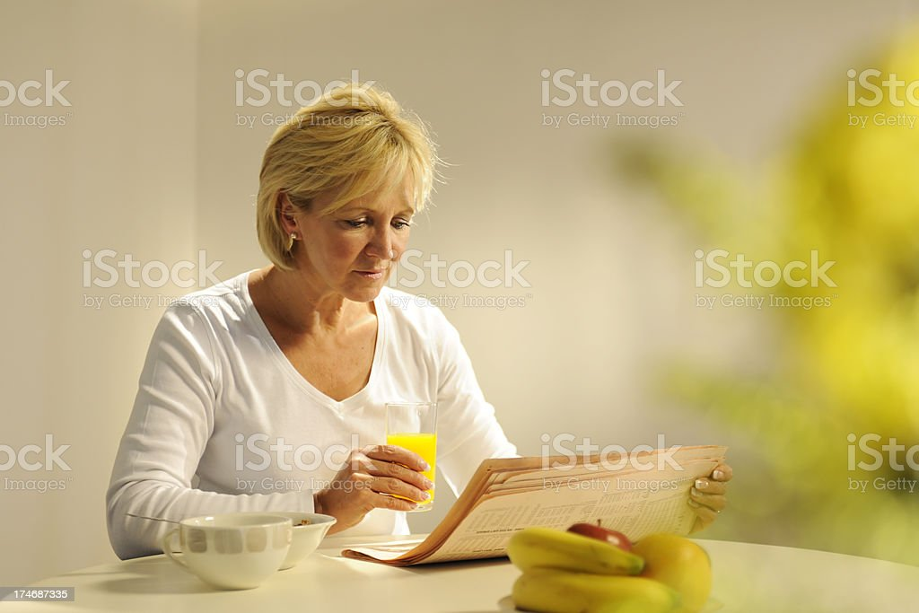 Mature Woman Eating Breakfast and Reading Newspaper royalty-free stock photo