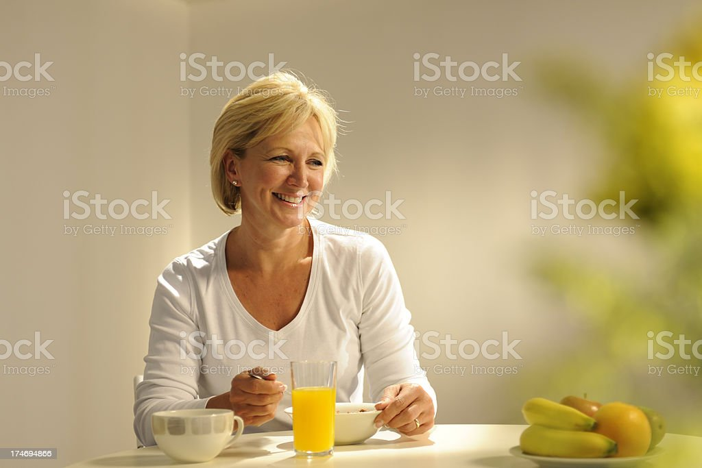 Mature Woman Eating Breakfast royalty-free stock photo