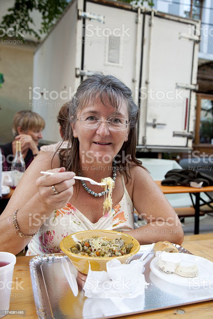 mature woman eating traditional meal at festival stock photo