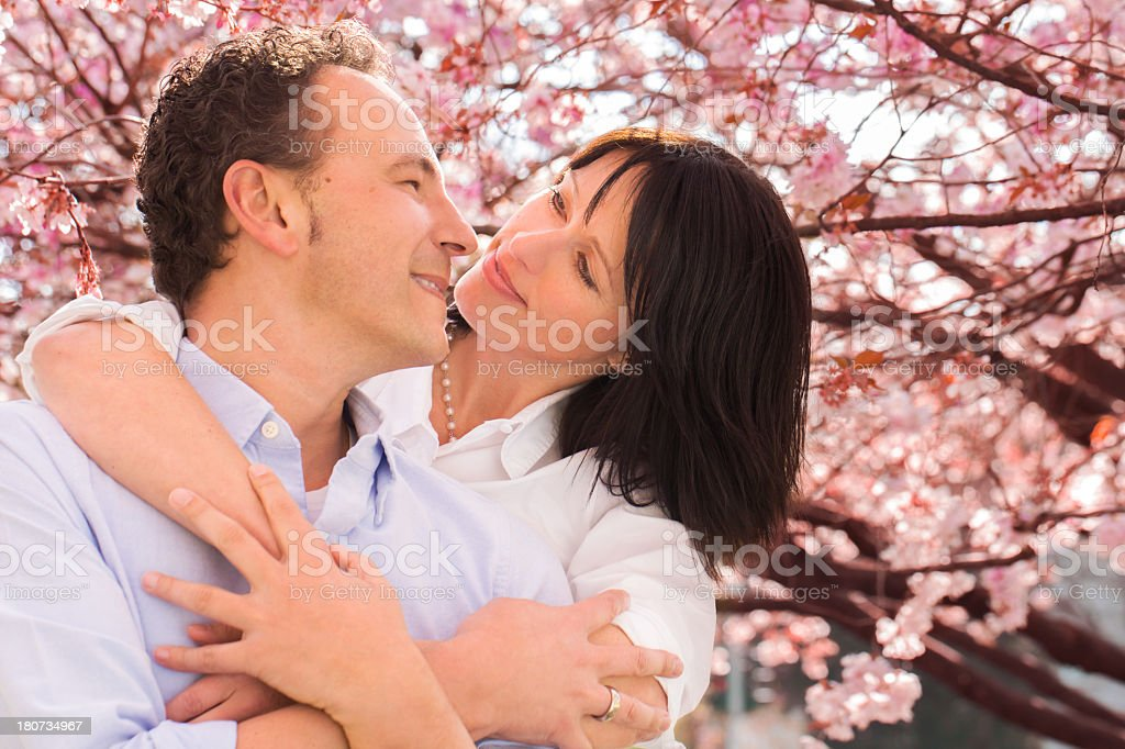 Mature woman embraces her husband in park royalty-free stock photo