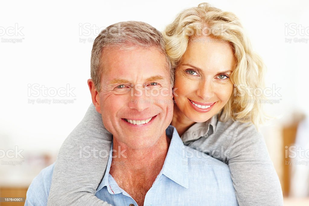 Mature woman embracing man from behind royalty-free stock photo