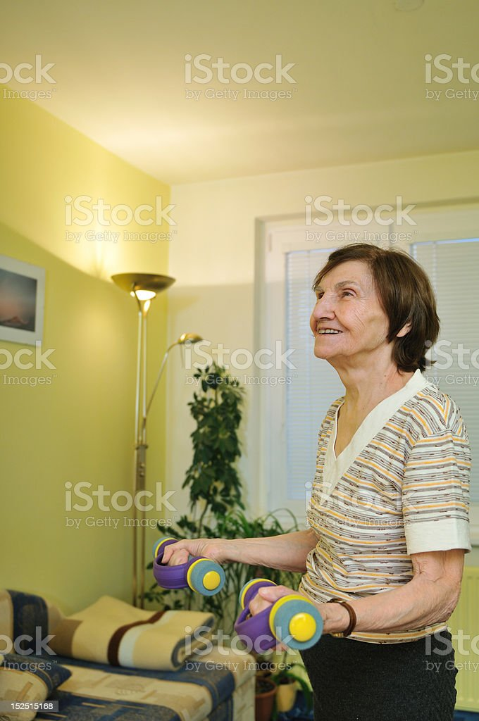 Mature woman exercises at home royalty-free stock photo