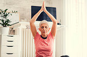 Mature Woman Exercises Yoga In Her Livingroom.
