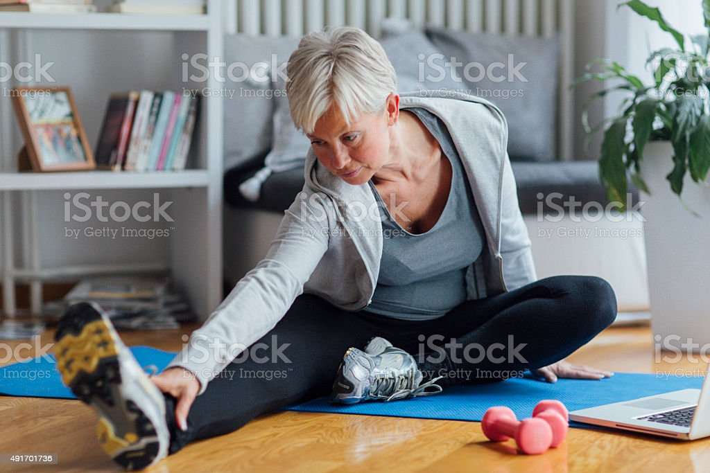 Mature Woman Exercising At Home. stock photo