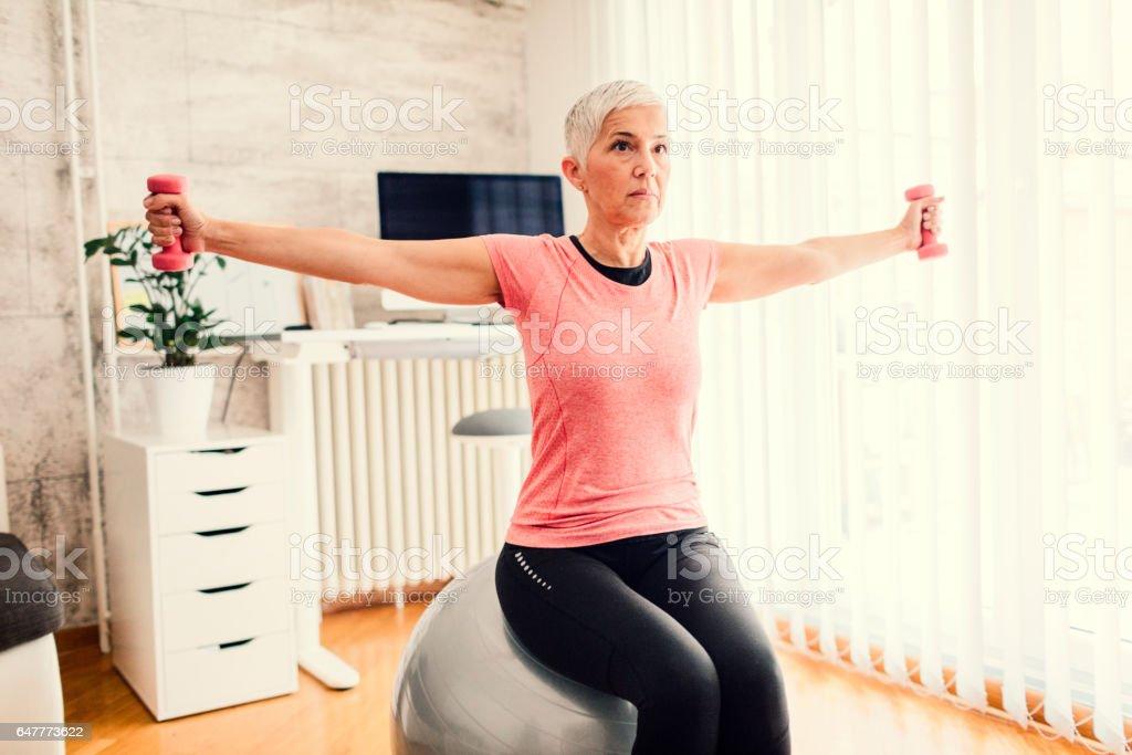 Mature Woman Exercising at Home stock photo
