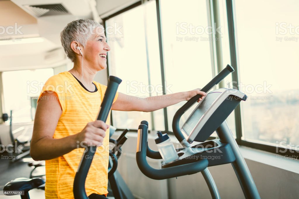 Mature Woman Exercising In Gym stock photo