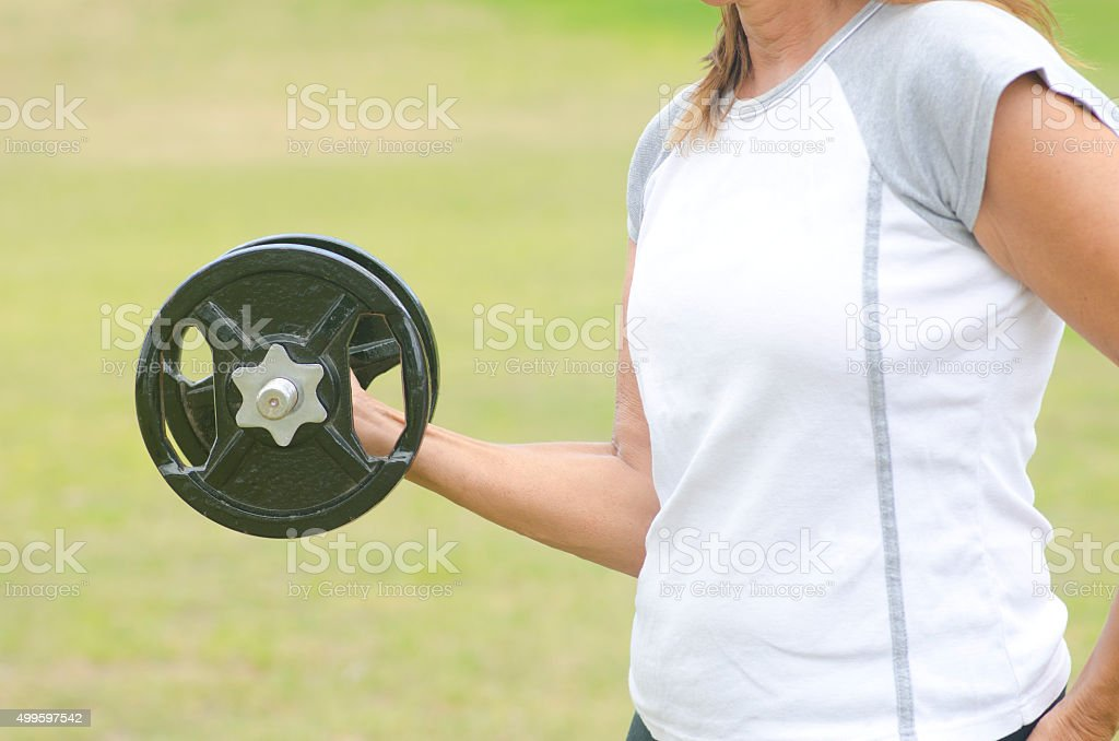 Mature woman exercising weight lifting outdoor stock photo