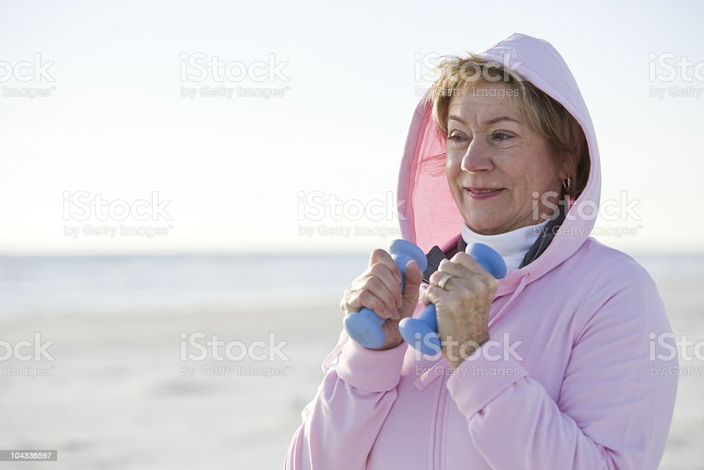Mature woman exercising with hand weights outdoors stock photo