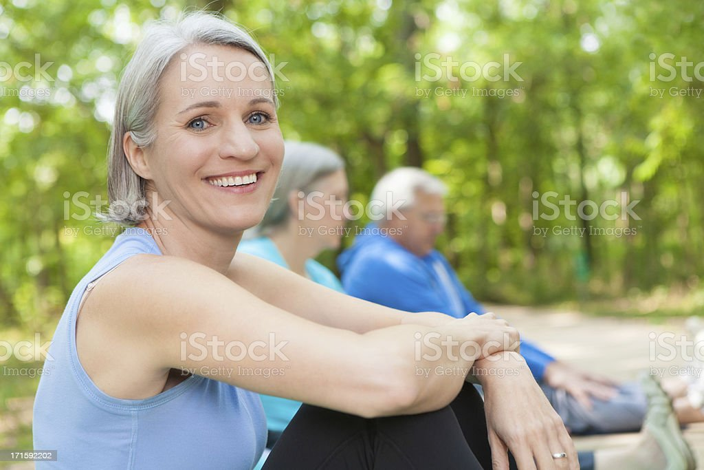 Mature woman exercising with outdoor senior fitness group royalty-free stock photo