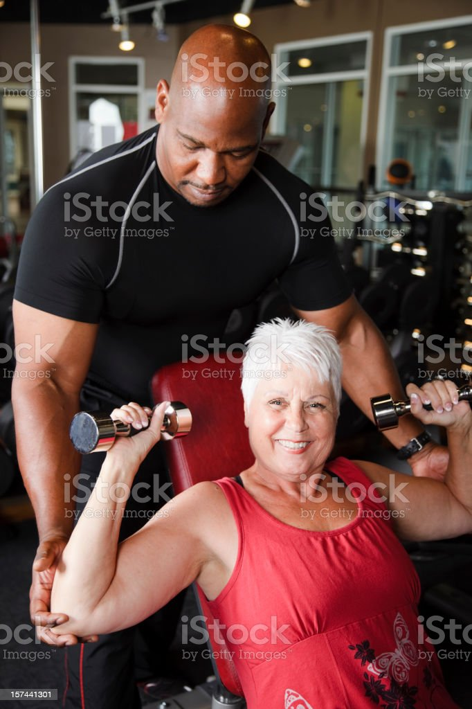 Mature Woman Exercising with Trainer royalty-free stock photo