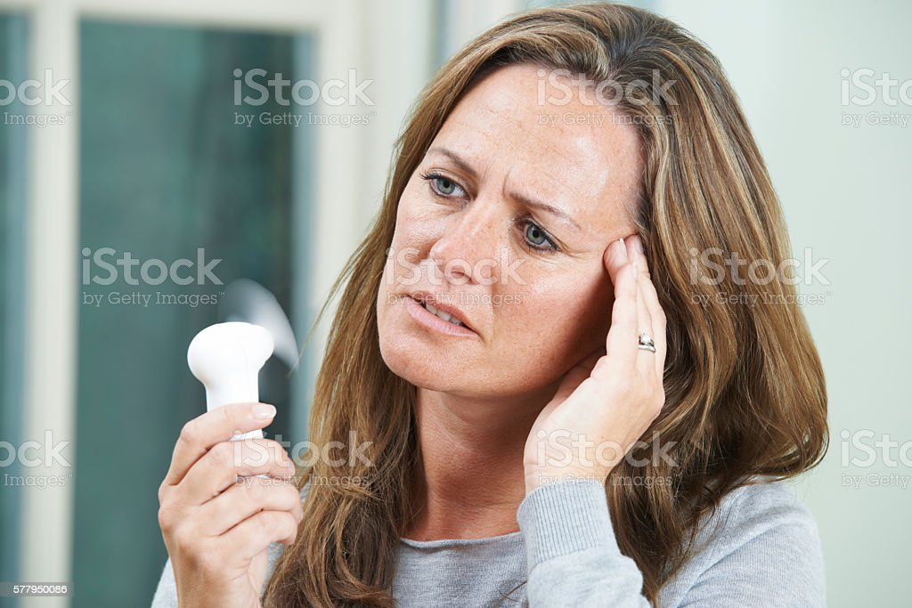 Mature Woman Experiencing Hot Flush From Menopause stock photo