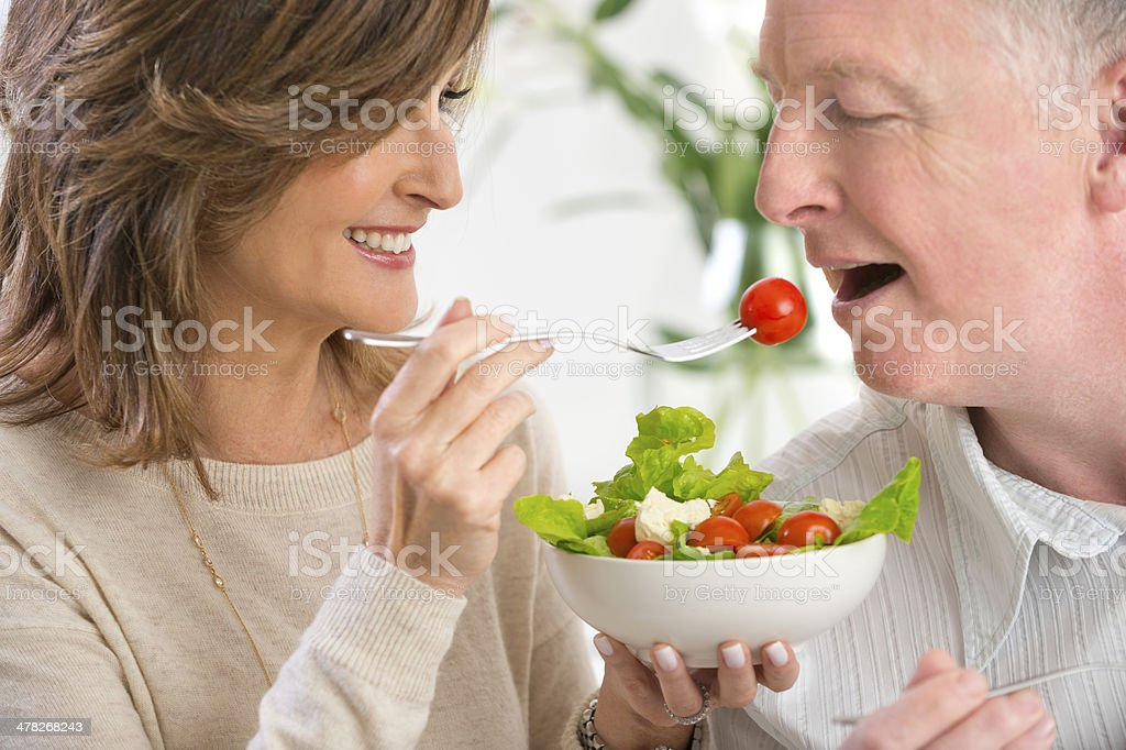 Mature woman feeding man salad royalty-free stock photo