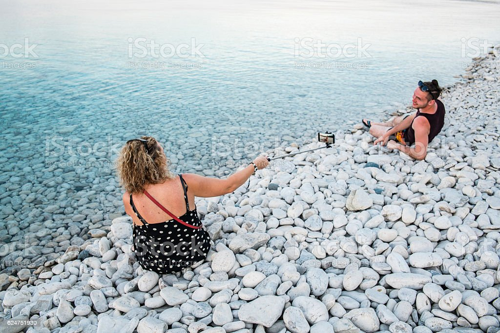 Mature woman filming young man at the shore. stock photo