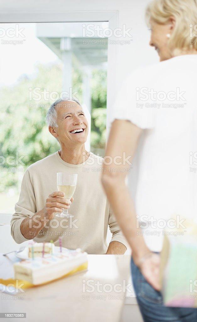 Mature woman giving surprise to senior man on his birthday royalty-free stock photo