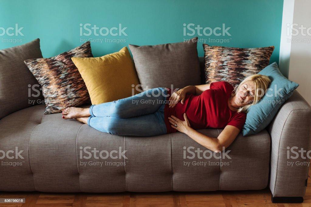 Mature woman has inflammatory pain in abdomen stock photo