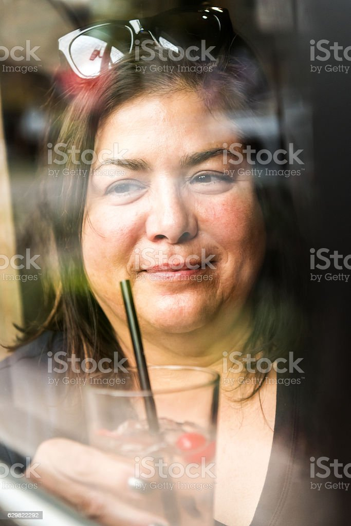 Mature woman having a drink stock photo