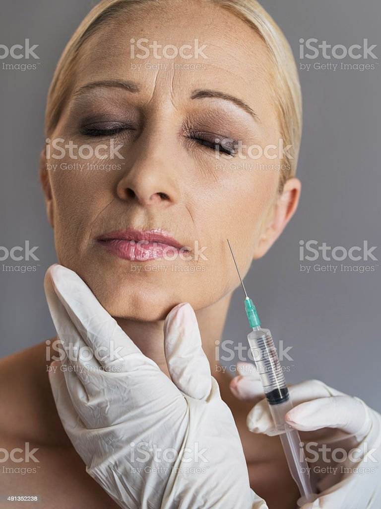 Mature woman having anti aging treatment with Botox. stock photo