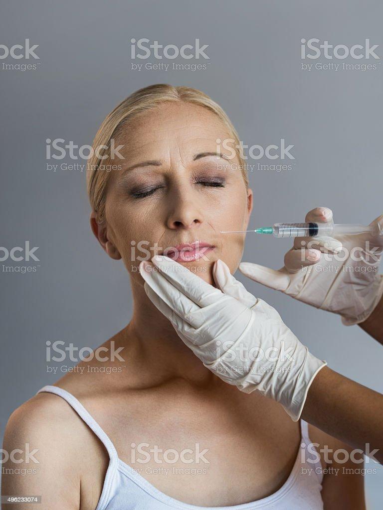 Mature woman having anti aging treatment with Botox. stock photo