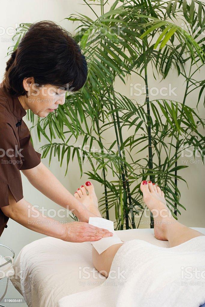 Mature woman having legs waxed stock photo