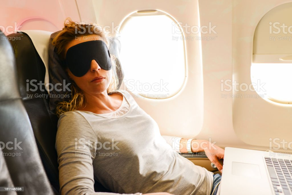 Mature Woman having nap in a plane stock photo