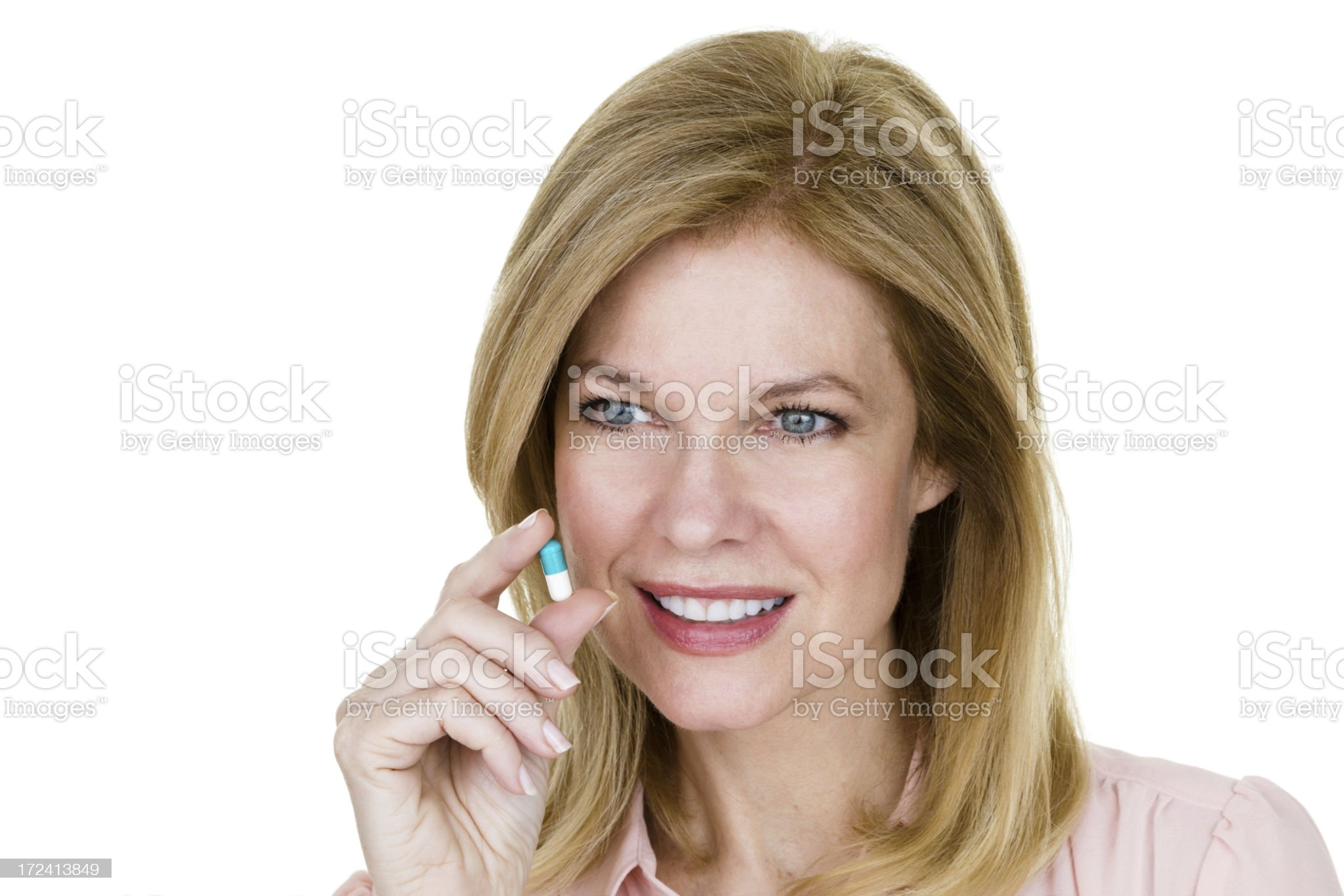Mature woman holding a pill royalty-free stock photo