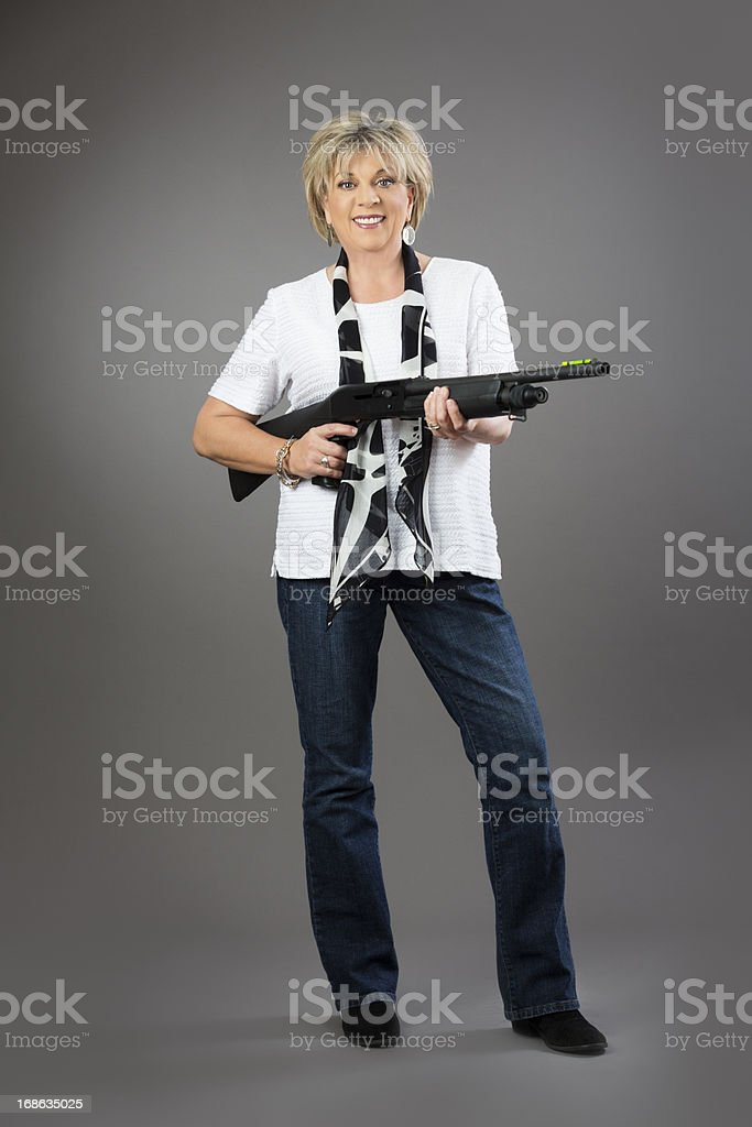 Mature woman holding a rifle on gray background royalty-free stock photo