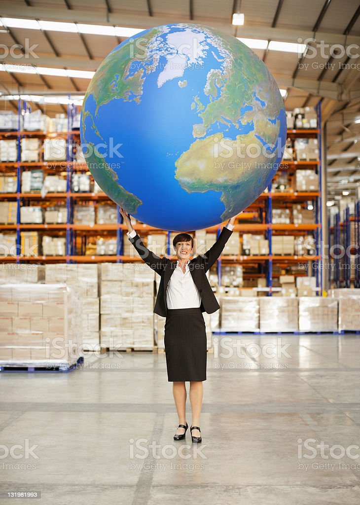 Mature woman holding aloft a large blue ball in warehouse stock photo