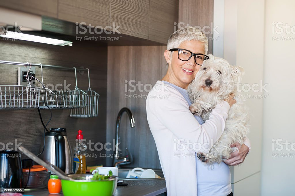 Mature woman holding dog at home stock photo