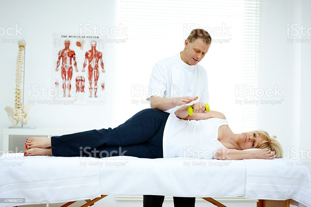 Mature woman holding dumbbell exercising with physiotherapist stock photo