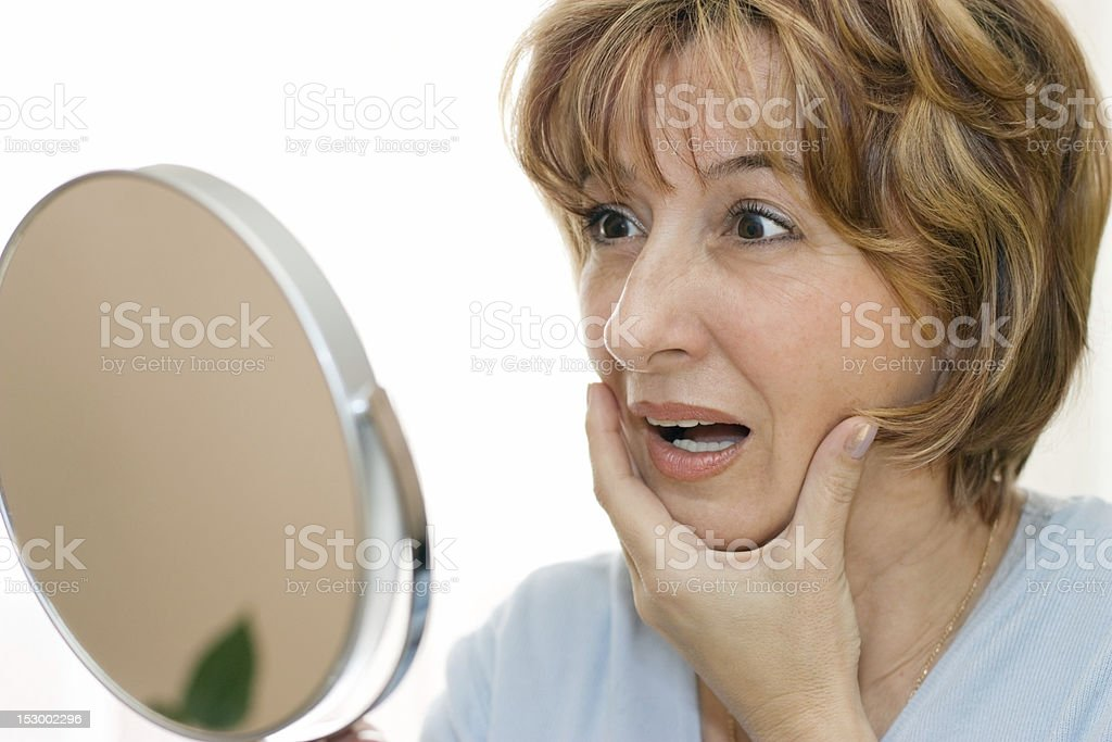 Mature woman holding face and looking into mirror, surprised royalty-free stock photo