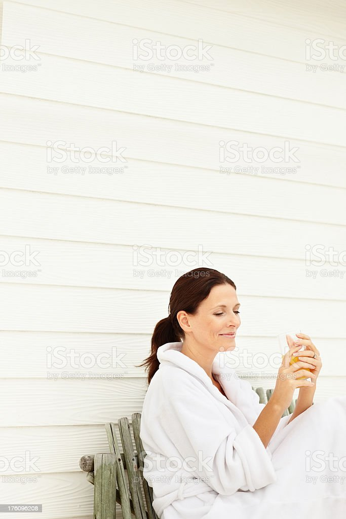 Mature woman holding glass of juice while sitting on bench royalty-free stock photo