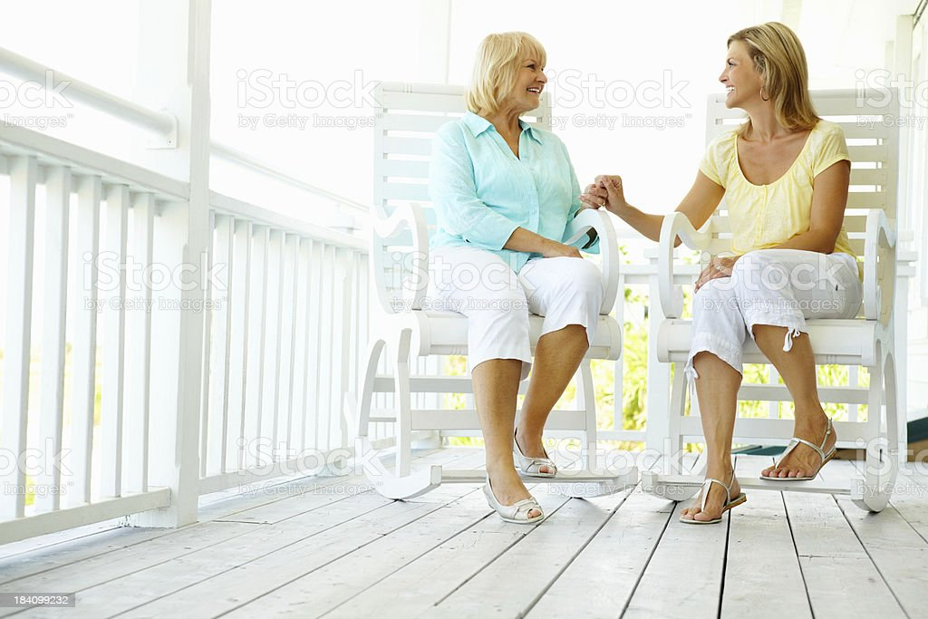Mature woman holding her daughter's hand on the porch stock photo
