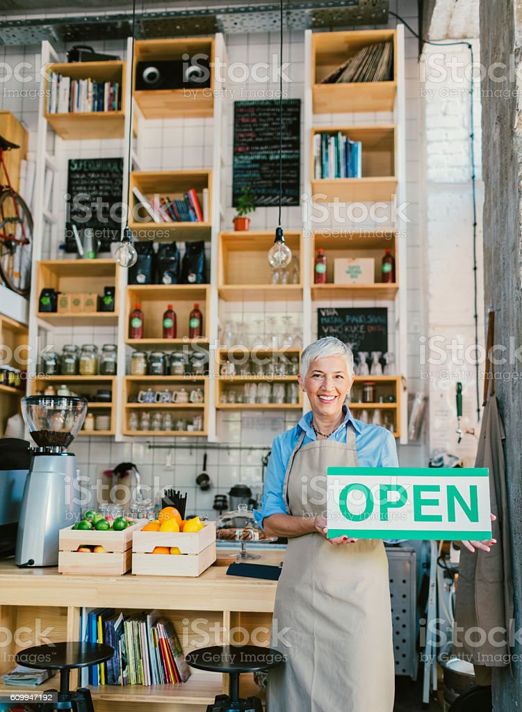 Mature Woman Holding Open Sign In Her Smoothie Cafe stock photo