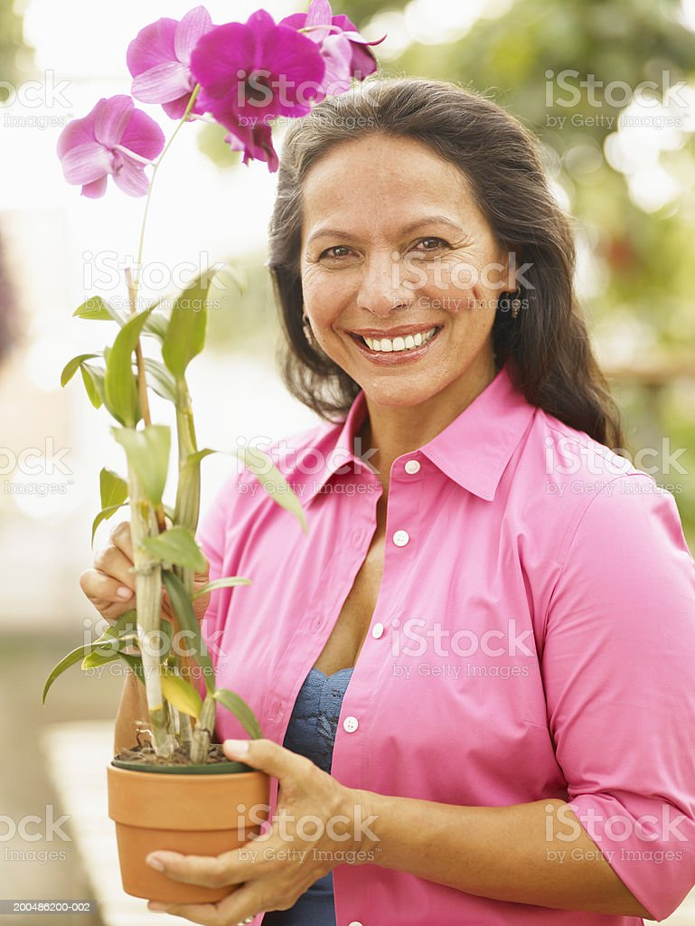 Mature woman holding potted orchid plant, smiling royalty-free stock photo