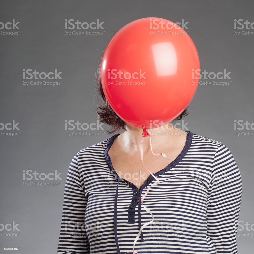Mature woman holding red balloon stock photo