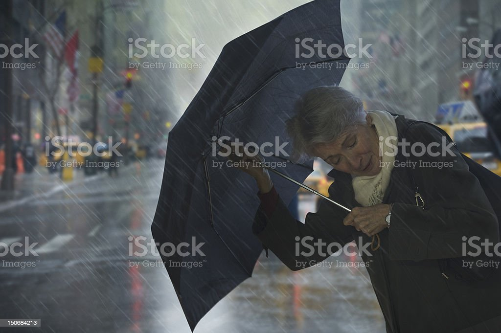 Mature woman holding umbrella against the wind royalty-free stock photo