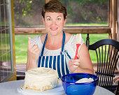Mature Woman Icing an Angel Food Cake.