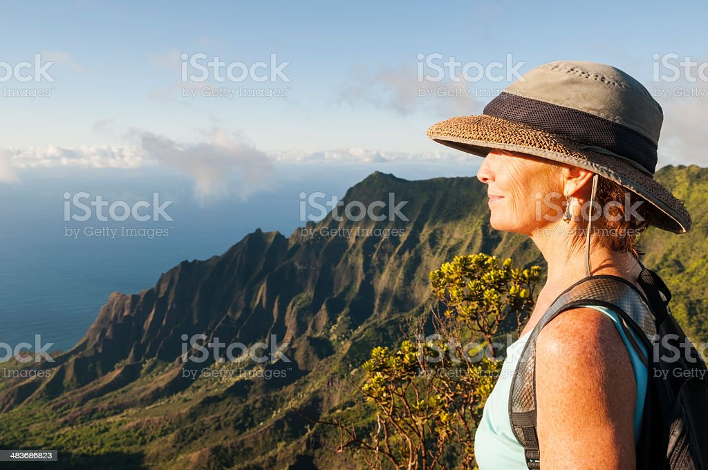 Mature woman in beautiful landscape at Kalalau Lookout, Kauai stock photo