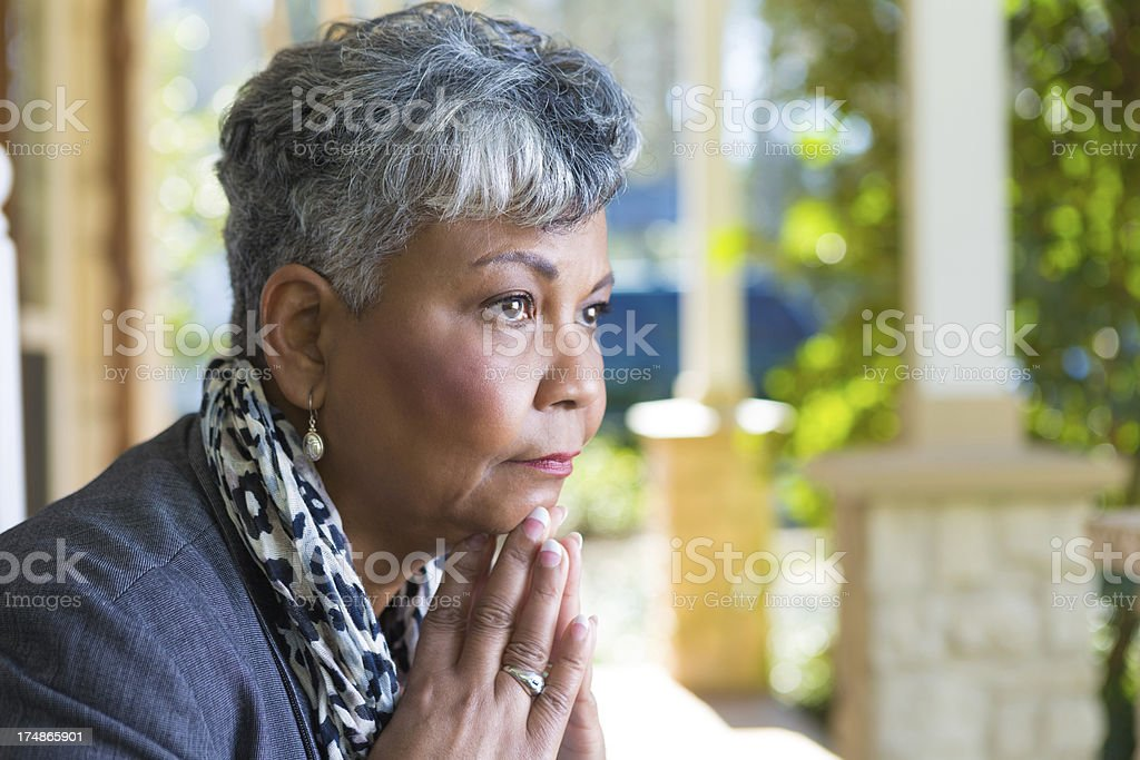 Mature woman in deep thought or prayer on front porch stock photo