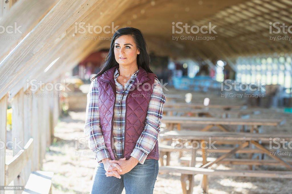 Mature woman in farm building, wearing plaid shirt stock photo
