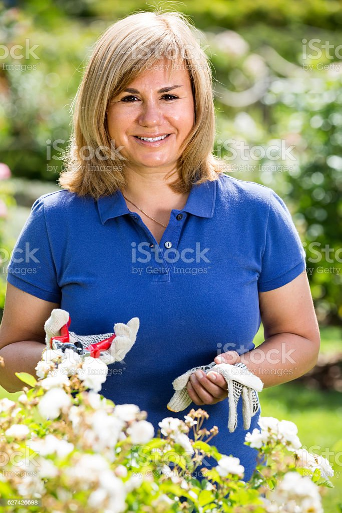 mature woman in garden on summer day stock photo