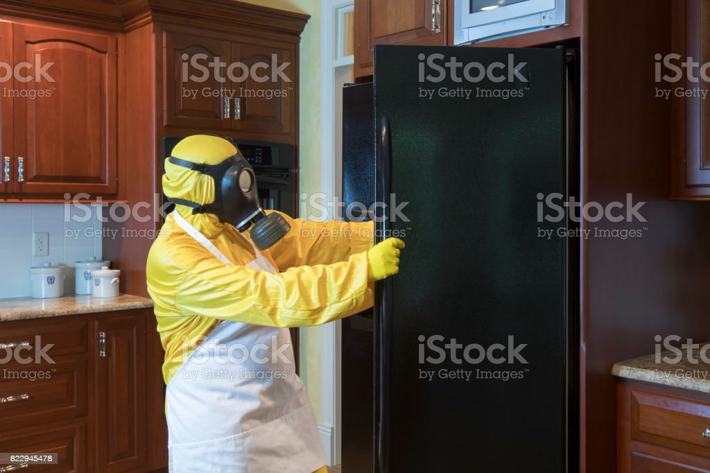 Mature woman in Haz Mat suit looking in refrigerator stock photo