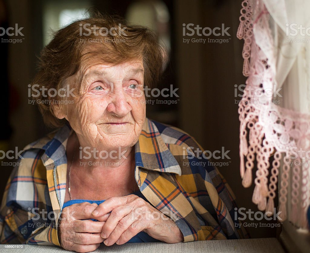 Mature woman in her home looking out the window. stock photo