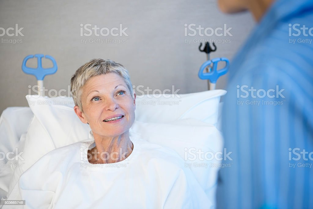 Mature woman in hospital bed smiling, portrait stock photo