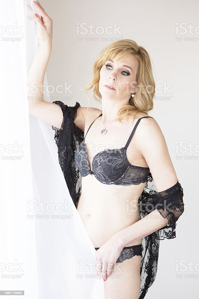 Mature woman in lingerie behind curtain. royalty-free stock photo