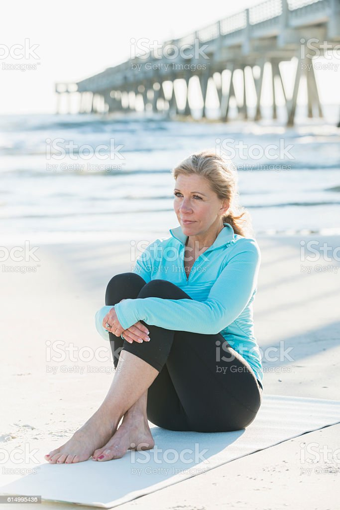 Mature woman in sports clothing sitting on beach stock photo