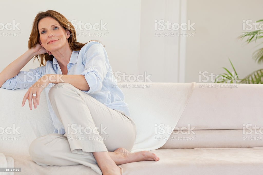 Mature woman in thoughts on sofa stock photo